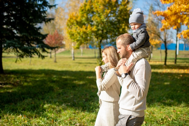 Happy family walking with their child on shoulders in sunny park.
