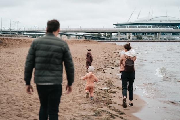 행복한 가족은 해안을 따라 걷는다. 아빠, 엄마, 두 아이가만을 따라 걷고 있습니다.