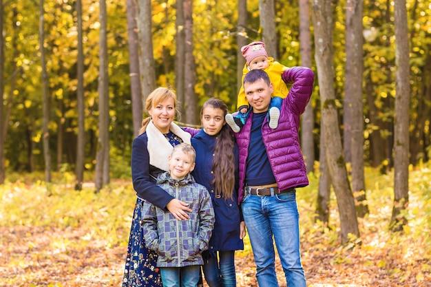 Happy family walks in autumn park
