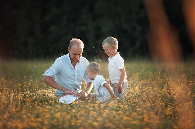 Счастливая семья гуляет по полю летом весело на закате