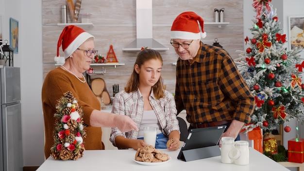 ホリデーシーズンを楽しんでいるタブレットコンピュータでオンラインクリスマス映画を見ている幸せな家族