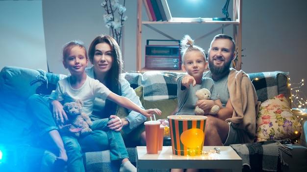 Счастливая семья смотрит проектор телевизионных фильмов с попкорном вечером дома, мама, отец и дети