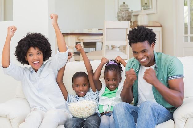 テレビを見ている幸せな家庭のポップコーン