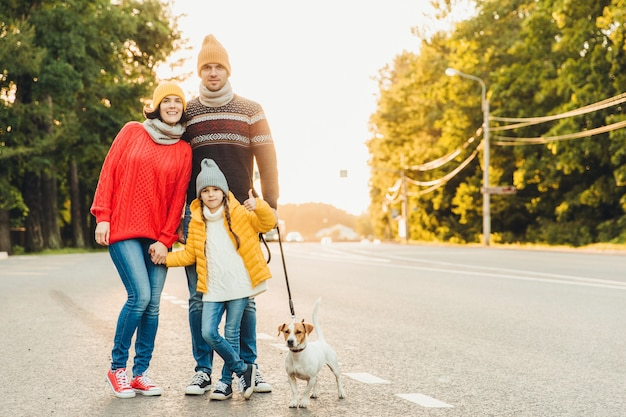 Happy family wear warm clothes walk with dog on road