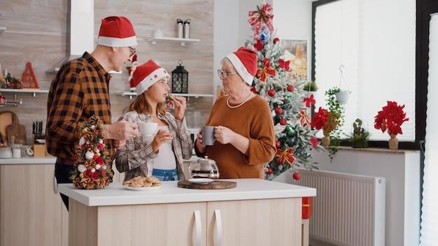 焼きたてのチョコレートクッキーを食べるクリスマスの休日を祝うサンタの帽子をかぶって幸せな家族