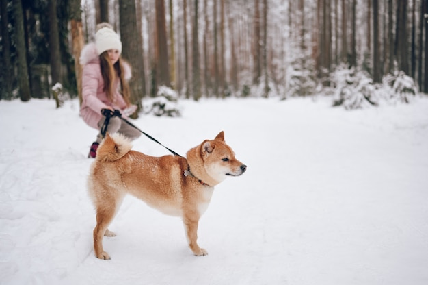 Happy family weekend - little cute girl in pink warm outwear walking having fun with red shiba inu dog in snowy white cold winter forest outdoors