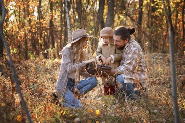 秋の森の中でベリーのバスケットを持つ幸せな家族