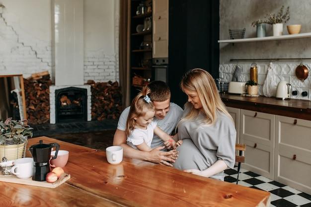 Счастливая семья с ребенком готовит и смеется на кухне