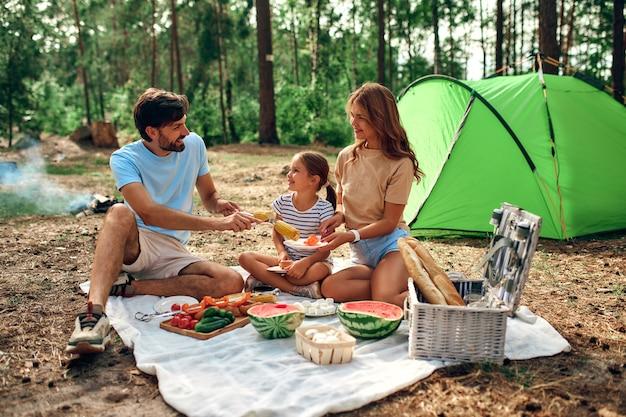 Счастливая семья с ребенком на пикнике сидят на одеяле возле палатки и едят жареную пищу и арбуз на выходных в лесу. походы, отдых, походы.