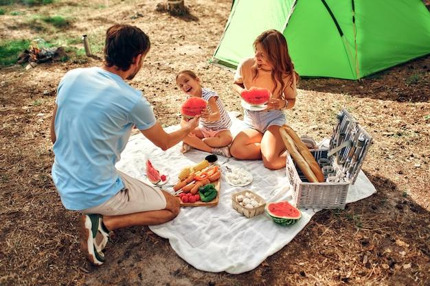 ピクニックに子供がいる幸せな家族は、テントの近くの毛布に座って、週末に森で揚げ物とスイカを食べます。キャンプ、レクリエーション、ハイキング。