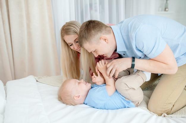 Счастливая семья с милым ребенком. мама, папа, сын играют на кровати в светлой уютной комнате дома.