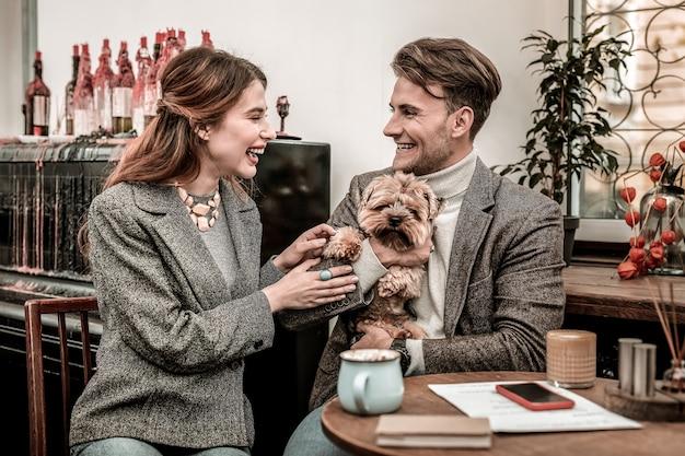 Счастливая семья с собакой. молодая семья шутит над своей собакой