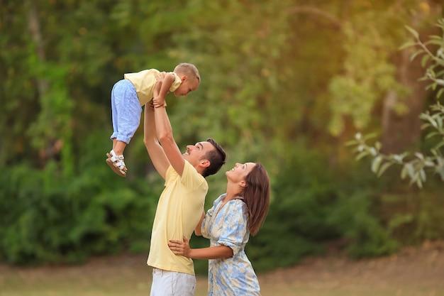 公園を散歩している小さな子供と幸せな家族