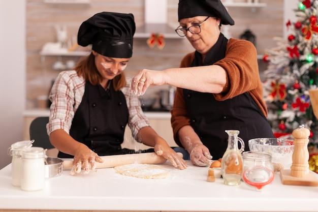 伝統的な生地料理クリスマスジンジャーブレッドデザートを作るエプロンと幸せな家族