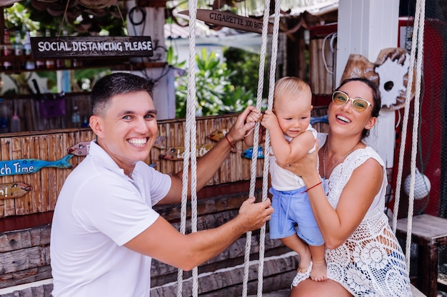 Happy family with a baby boy on swing outside hotel