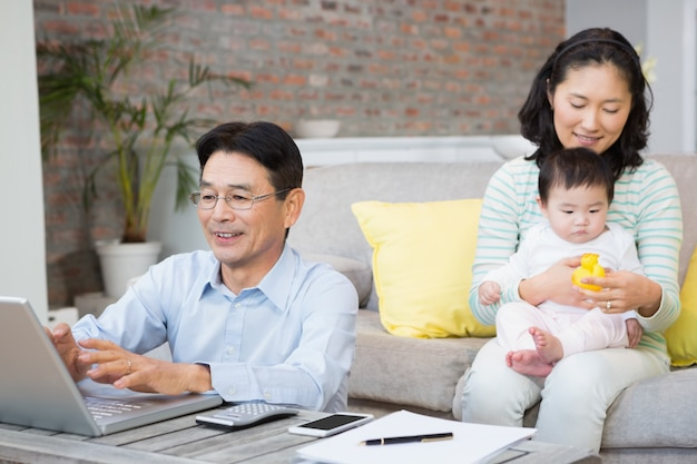 Happy family with baby daughter in the living room counting bills