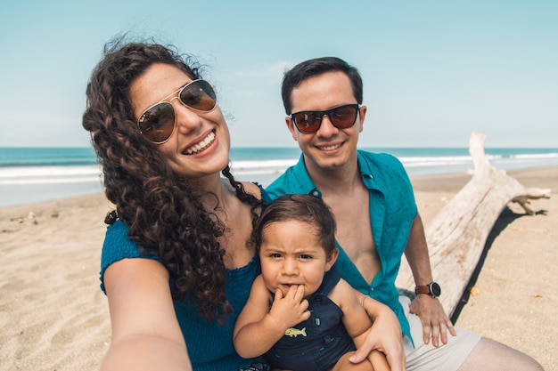 Happy family with baby taking selfie on beach in summer day