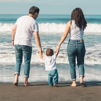 Счастливая семья с ребенком, гуляя по пляжу и глядя на море