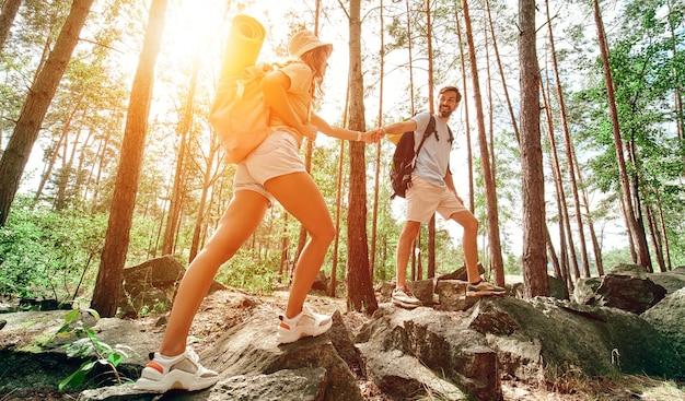배낭과 래브라도 개가 있는 행복한 가족이 숲을 걷습니다. 캠핑, 여행, 하이킹.