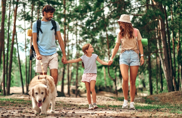 Happy family with backpacks and labrador dog are walking in the forest. mom dad and their daughter on the weekend. camping, travel, hiking.