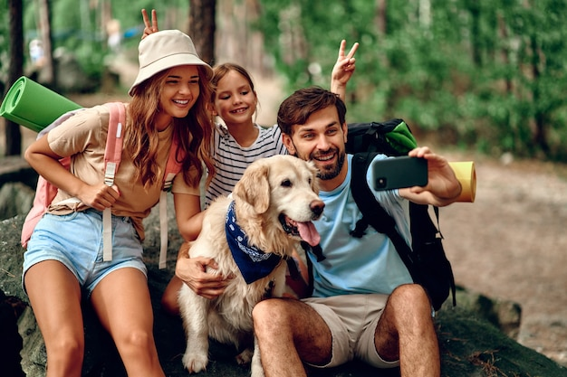 Happy family with backpacks and labrador dog walks in the forest. camping, travel, hiking.