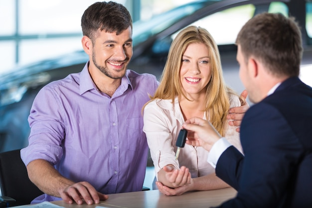 Happy family with car dealer in auto show or salon buy a car