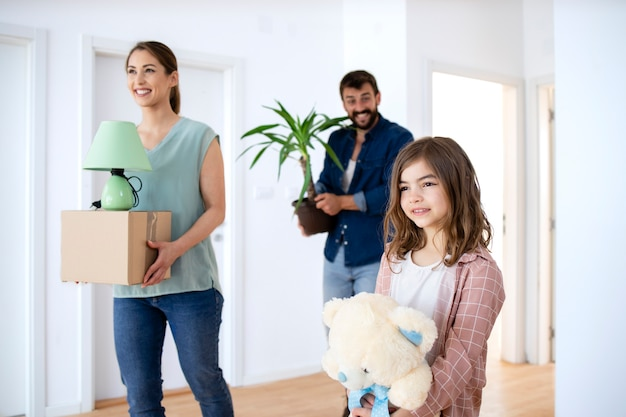 Happy family with cardboard boxes flowers and toys at their new house real estate.