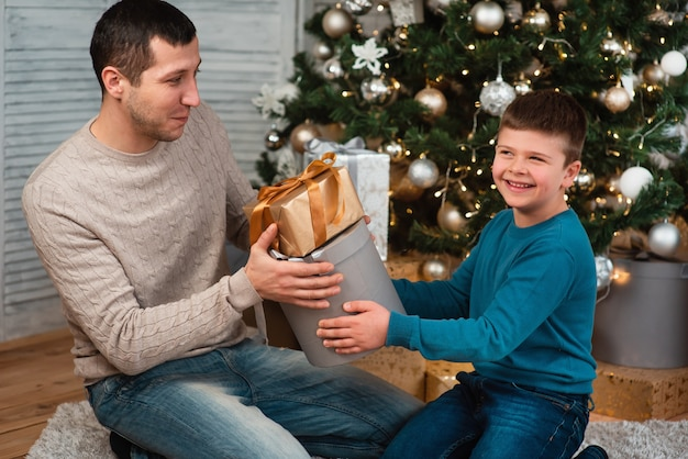 A happy family with a child celebrates a new year or christmas. father and son sit on the floor near the christmas tree in a home setting and exchange gifts