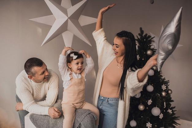 飾られたクリスマスツリーと花輪で新年とクリスマスを祝う子供と幸せな家族