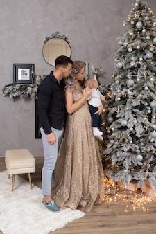 장식된 크리스마스 트리 근처에서 집에서 함께 시간을 보내는 행복한 가족