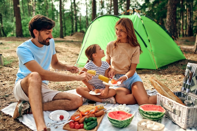 Happy family with a child on a picnic sit on a blanket near the tent and eat fried food and watermelon during the weekend in the forest. camping, recreation, hiking.