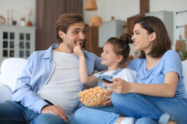 Счастливая семья с ребенком, сидящим на диване, смотрящим телевизор и едящим попкорн, молодые родители обнимают дочь, отдыхая на диване вместе.