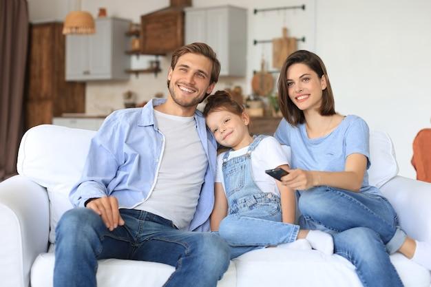Счастливая семья с ребенком, сидящим на диване, смотрящим телевизор, молодые родители, обнимая дочь, вместе отдыхая на диване.