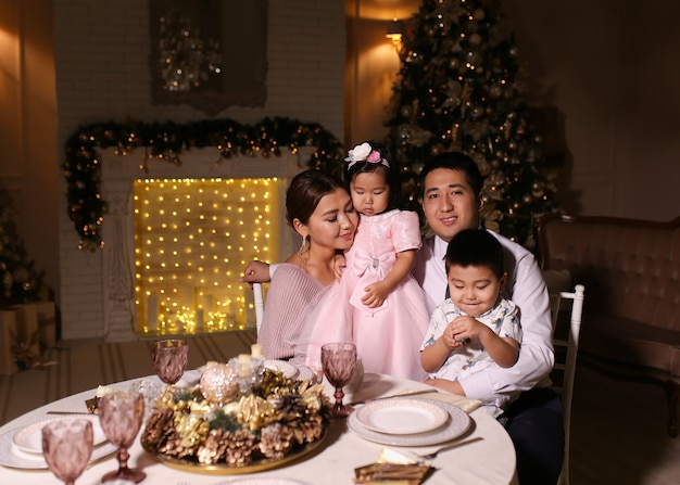 Happy family with children celebrating christmas dinner by the fireplace fireplace in the evening