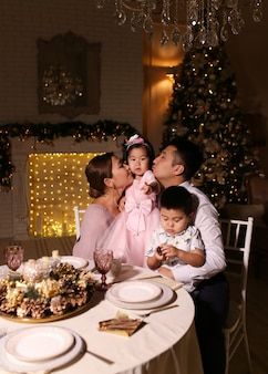 Happy family with children celebrating christmas dinner by the  tree in the evening