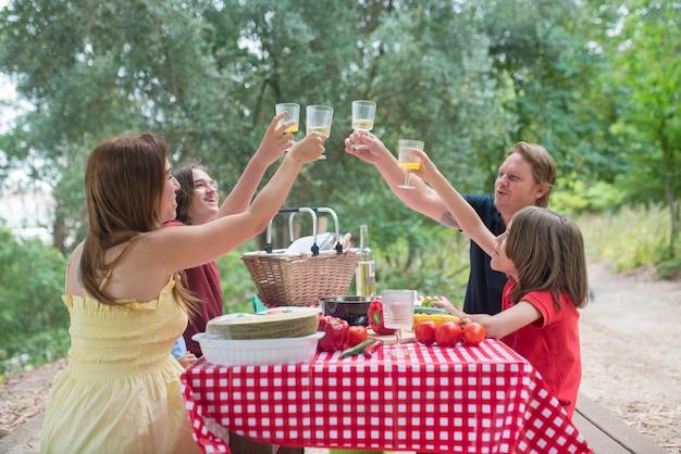 応援してジュースを飲んでいる子供たちと幸せな家族。食べ物や飲み物を楽しんでいる息子と一緒にテーブルの周りに座っている中年の大人の両親