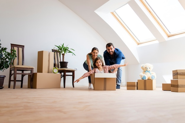 Happy family with children enjoying very first day in new house and riding in cardboard boxes