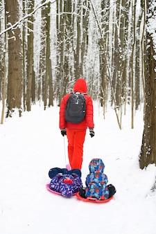 Счастливая семья с детьми весело проводит зимние каникулы в заснеженном зимнем лесу. отец катает своих детей брата и сестру на санях с блюдцем