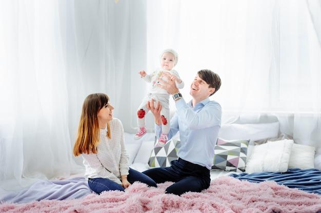 Счастливая семья с детьми в спальне