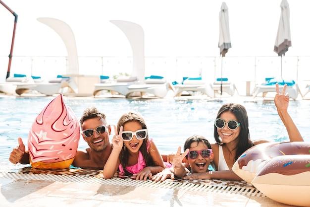 旅行や休暇中にゴム製のリングで、プールで泳いでサングラスをかけている子供たちと幸せな家族