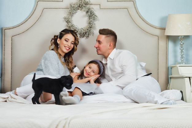 Happy family with christmas gifts on floor at home on merry christmas and happy new year. family with dog having fun near xmas tree in bedroom on bed. lovely parents give dog to daughter. copy space