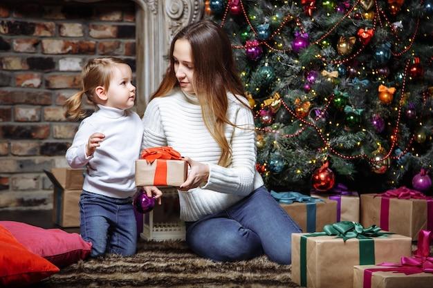 クリスマスツリーの近くにクリスマスプレゼントと幸せな家族