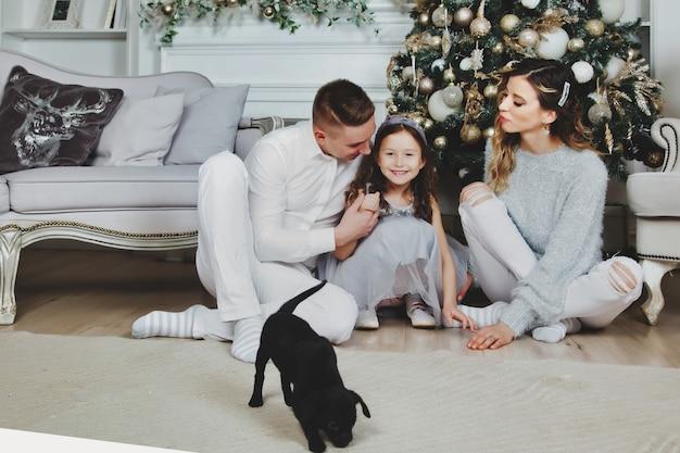 Счастливая семья с рождественскими подарками на полу дома с рождеством и новым годом. семья с собакой с удовольствием возле елки в гостиной. милые родители отдают собаку дочери. копировать пространство