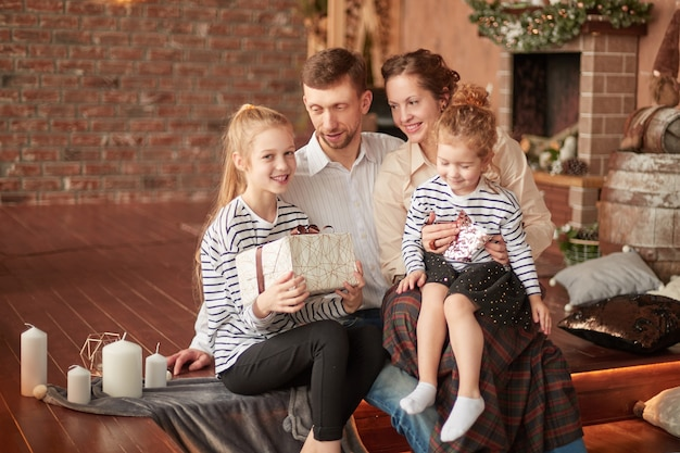 Happy family with christmas gifts sitting in a cozy living room.