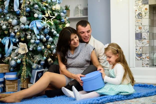 リビングルームでクリスマスプレゼントで幸せな家族。