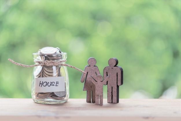 Счастливая семья с монетами в стеклянной банке на деревянный стол