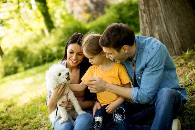 Счастливая семья с милой собакой бишон в парке
