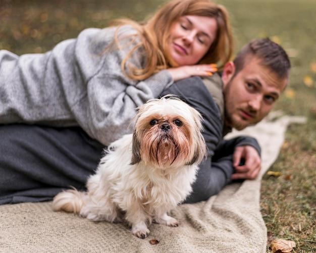Счастливая семья с милой собакой на одеяле