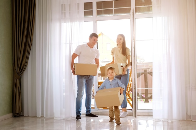 Happy family with cute son in blue shirt enters door moving to new house holding big boxes against panoramic windows