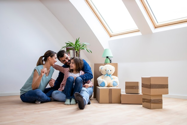 Happy family with daughter sitting on the parquet floor and celebrating moving into new home